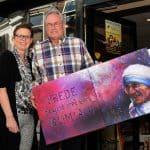 Bestuurslid van Cantica Sacra Henk Brandsma overhandigt geportretteerde peacmaker aan Helma Vredenburg, één van de winkeliers bij wie een portret in de etalage hangt.