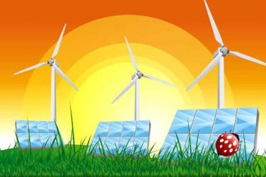 Panels with solar cells and wind generators on a green field with blue sky stock photo